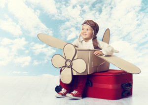 Little boy with cardboard box airplane sitting on suitcase with pilot hat and glasses